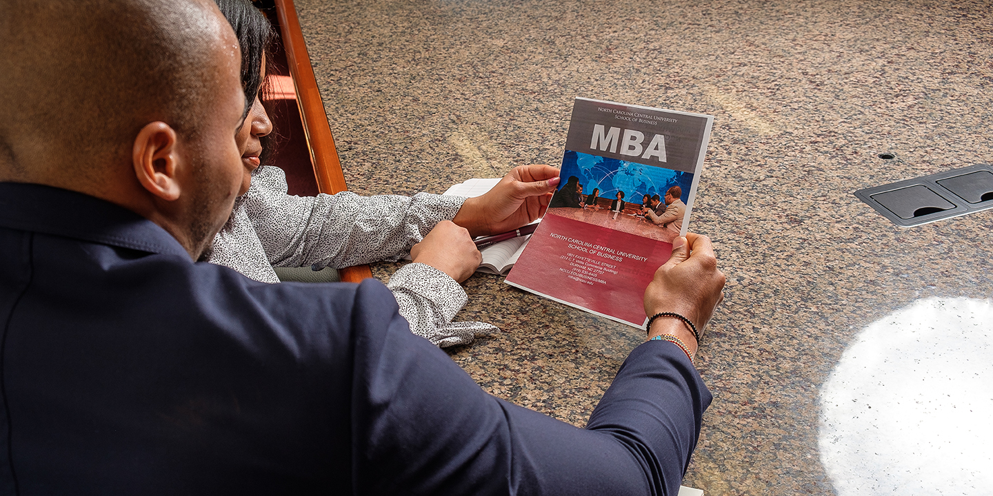 Students looking at MBA booklet.