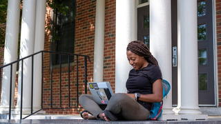 Student sitting outside building working on laptop