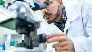 man in white coat looking into a microscope