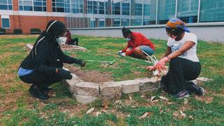 Workers weed the Campus Garden wearing gloves and facemasks.