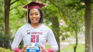 Volleyball player wearing graduation cap while holding volleyball.