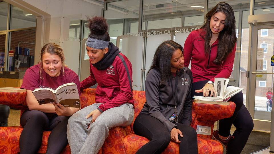 Four NCCU student athletes sitting in the library.