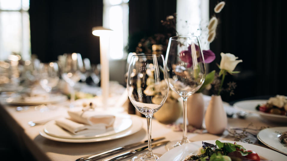 A place setting at a dining table with dishes, napkins, glasses and silverware.