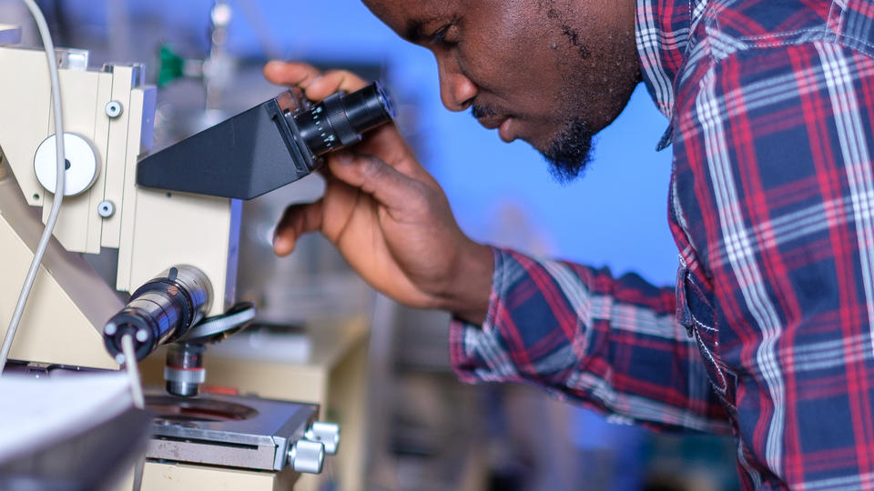 Man is looking into a microscope in a laboratory setting.