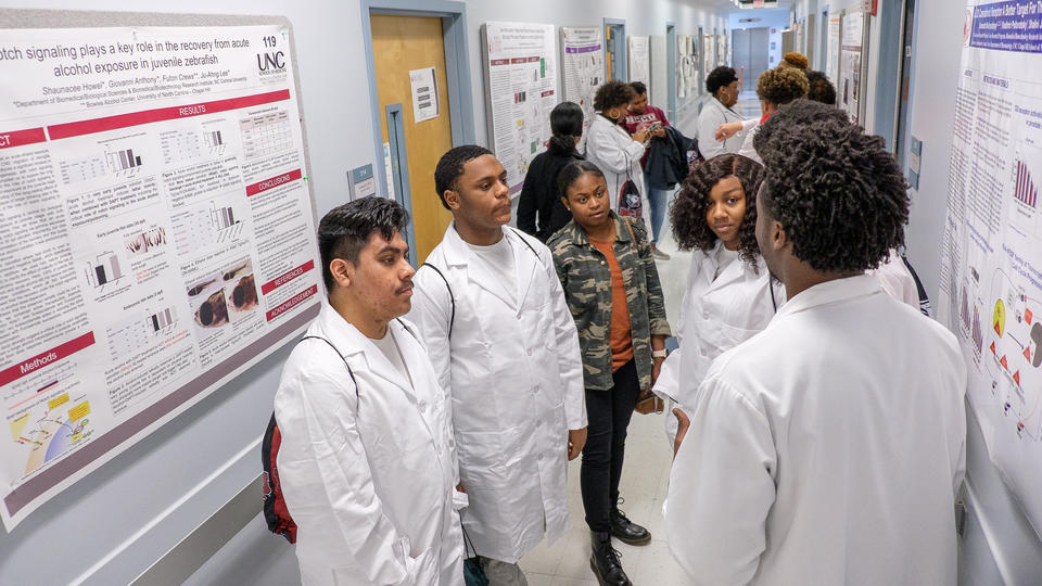 A dozen students stand in the hallway of a research laboratory.