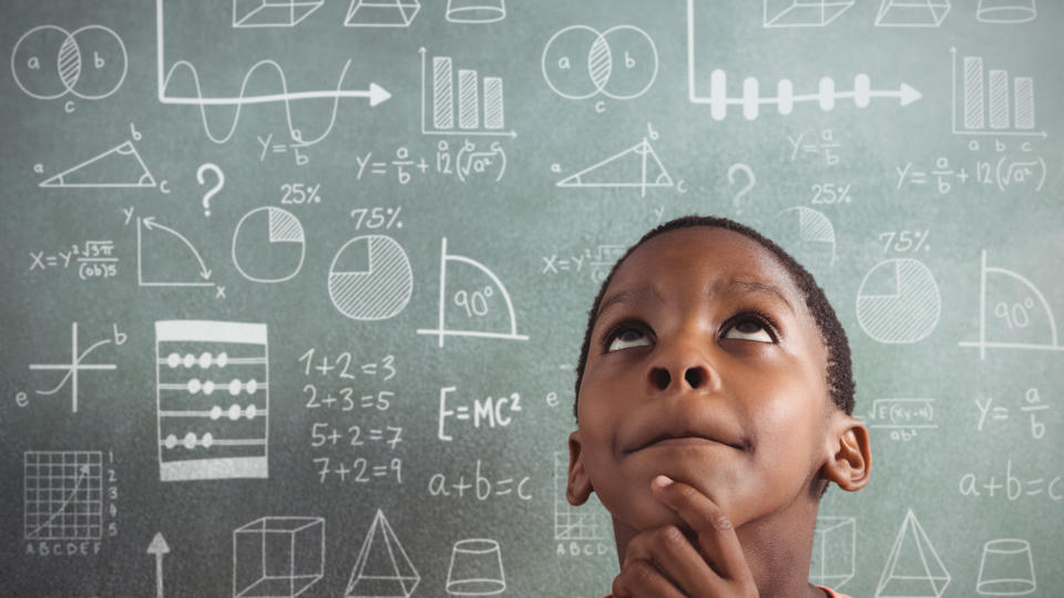 Boy standing in front of a chalkboard with mathematic equations